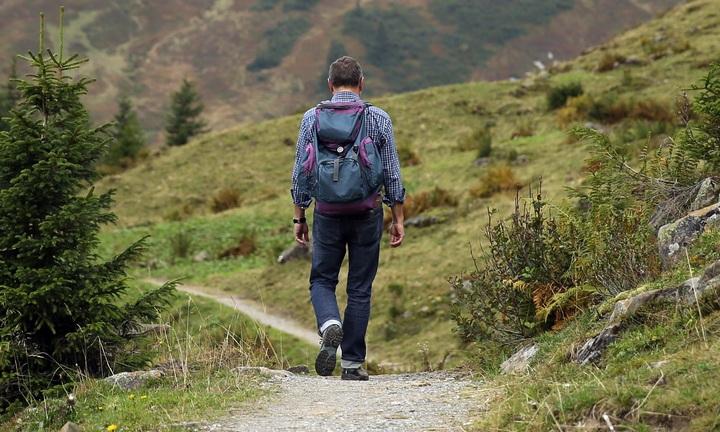 Hombre mochilero caminando por un sendero