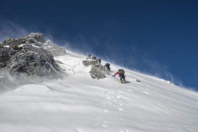 Escaladores subiendo una montaña nevada